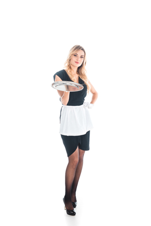 attractive housemaid in black uniform, apron and stockings standing with tray on white background