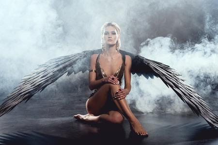 schöne Frau mit schwarzen Engelsflügeln sitzt, schaut in die Kamera und posiert auf dunklem Hintergrund