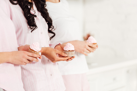 cropped view of girls in nightwear holding cupcakes with copy space