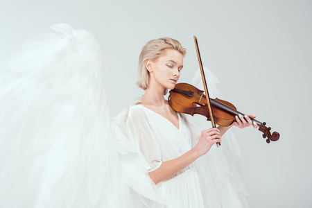 beautiful woman in angel costume with wings playing violin isolated on white