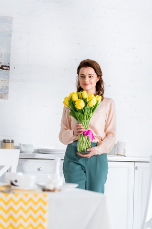 Blissful brunette woman holding bouquet of yellow tulips in kitchen