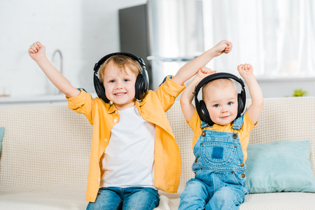 adorable brothers in headphones looking at camera and cheering with hands in air at home 스톡 콘텐츠