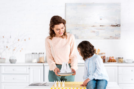 Smiling mother showing folded napkins to daughter in kitchen 写真素材