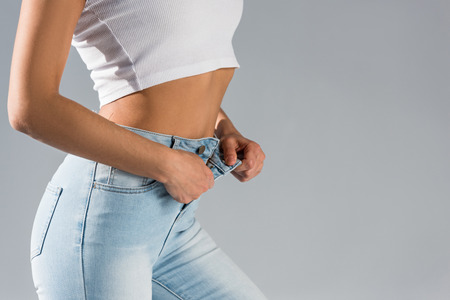Cropped view of shapely girl unzipping jeans isolated on grey