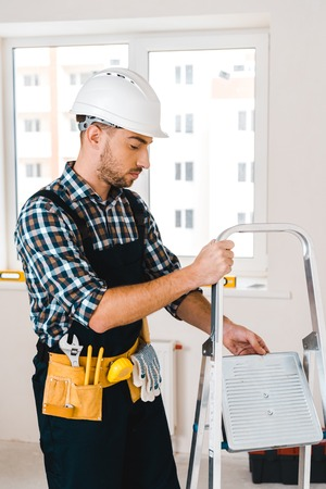 handsome handyman in helmet holding ladder in room Stockfoto - 119039491