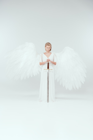 beautiful woman with angel wings holding sword and posing on white background