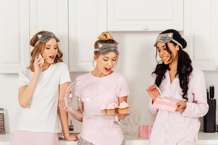 beautiful multicultural girls using smartphone, holding cupcakes and gift box during pajama party in kitchen