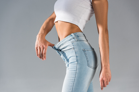 Cropped view of slim young woman in jeans isolated on grey 版權商用圖片