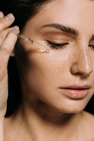 Atractiva mujer joven aplicando suero en la cara con pipeta