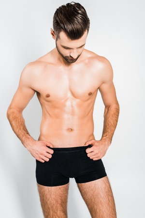 handsome muscular man in black underwear posing isolated on grey