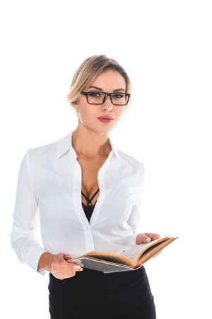 blonde teacher in blous with open neckline, glasses and skirt holding book isolated on white Standard-Bild