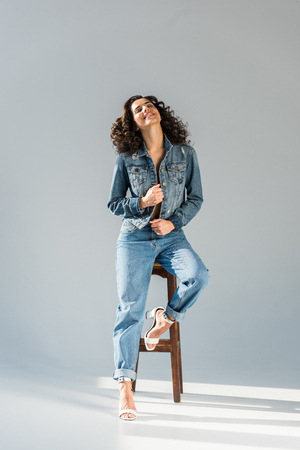Blissful young woman in jeans and jacket sitting on wooden chair on grey background Reklamní fotografie