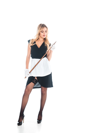 attractive housemaid in black uniform, apron, stockings standing with pointer on white background