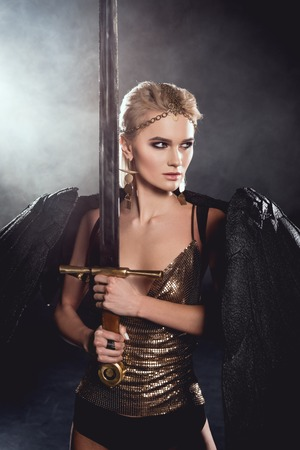 beautiful woman in warrior costume with black angel wings holding sword and posing on dark smoky background Reklamní fotografie