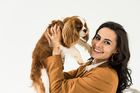 Cheerful brunette woman in brown jacket holding dog isolated on white