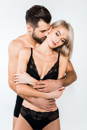 beautiful tender couple in black underwear embracing isolated on grey