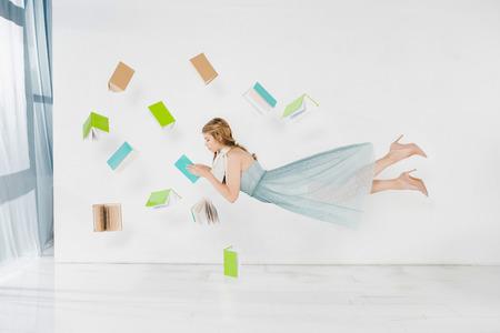 Chica flotante en vestido azul libro de lectura en el aire sobre fondo blanco. Foto de archivo
