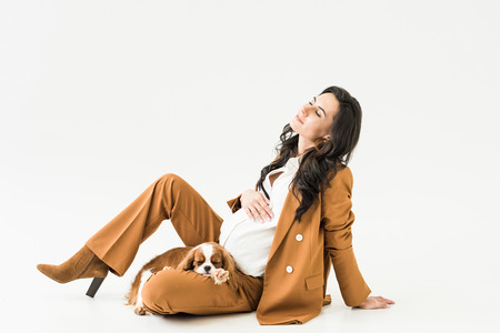 Dreamy pregnant woman sitting on floor with sleeping dog on white background