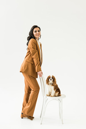 Amazing pregnant woman in suit standing near dog on chair on white background