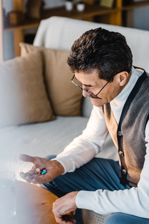 senior man looking at pills in hand while sitting at home