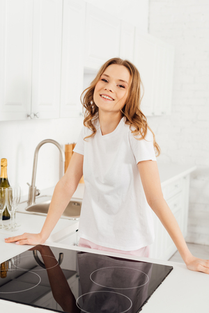 beautiful smiling girl in pajamas near induction cooker looking at camera in kitchen