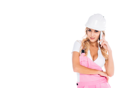 handy woman in pink uniform, hardhat standing and talking on smartphone isolated on white