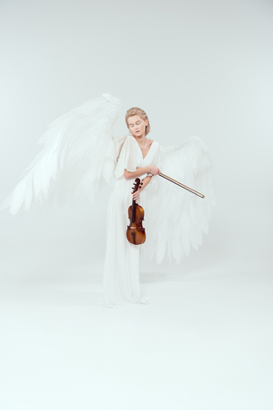 beautiful woman in angel costume with wings holding violin and bow isolated on white