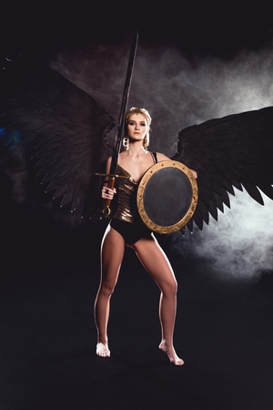 beautiful woman in warrior costume and angel wings looking at camera while posing with shield and sword on black background