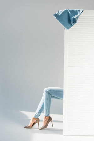 Partial view of woman in jeans sitting behind room divider on grey background Reklamní fotografie