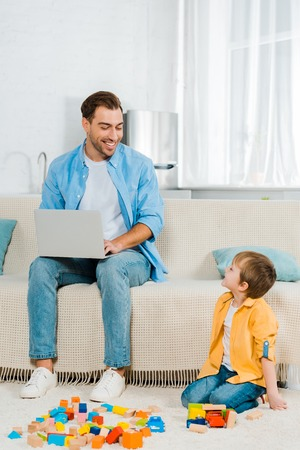 smiling father sitting on couch and using laptop while preschooler son playing with colorful building blocks at home