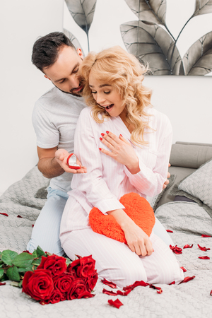 Man sitting on bed with red roses and proposing to surprised girlfriend Stock Photo
