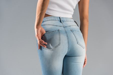 Cropped view of shapely girl in blue jeans isolated on grey Reklamní fotografie