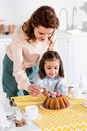 Mother and daughter decorating easter cake with painted eggs in kitchen