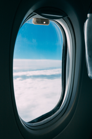 airplane window with view of blue cloudy sky