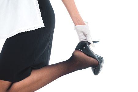 cropped view of housemaid in black uniform, gloves and apron holding on shoe heel isolated on white