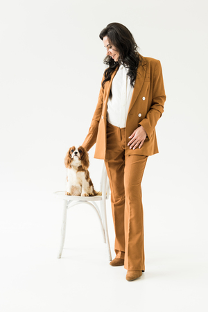 Pregnant woman in elegant brown suit stroking dog on white background