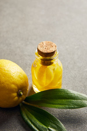 Ripe lemon with green leaves and glass bottle with essential oil on dark surface