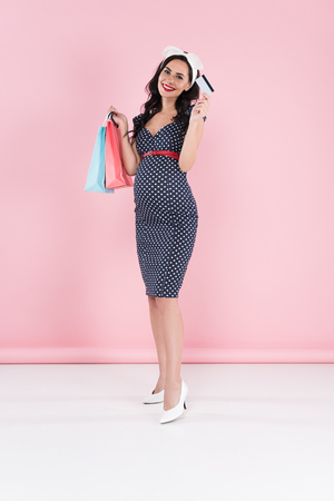 Blissful pregnant woman in dotted dress holding shopping bags and credit card on pink background