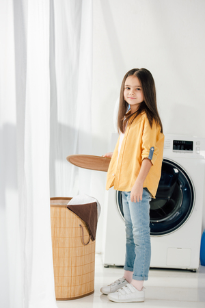child standing near washer and holding basket cover in laundry room Archivio Fotografico