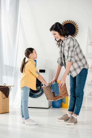 daughter in yellow shirt and mother in grey shirt holding basket and smiling in laundry room Imagens