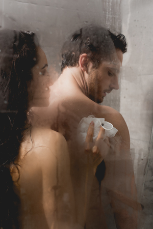 selective focus of naked man and attractive woman taking shower with loofah Фото со стока