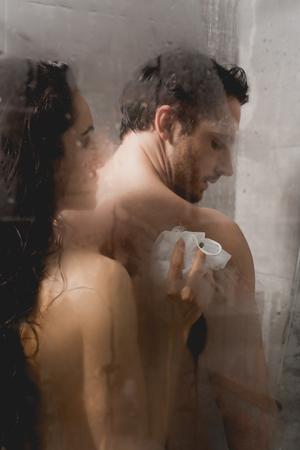 Selektiver Fokus von Mann und attraktiver Frau beim Duschen mit Luffa