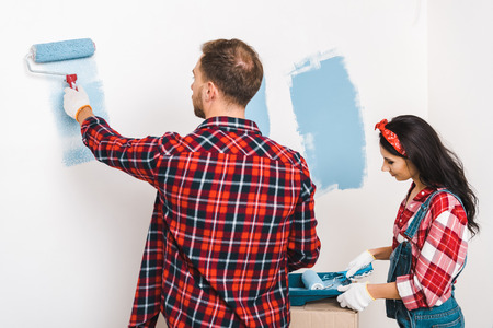 man and woman painting wall in blue color at home Standard-Bild - 118994952