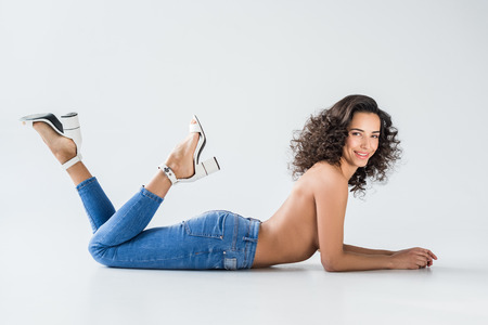 Sexy girl in jeans with nude breasts lying on grey background Banque d'images