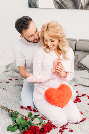 Smiling man sitting on bed with roses and presenting gift to girlfriend Stock Photo