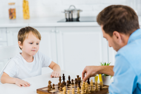 father and preschooler son sitting at table and playing chess at home