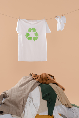 t-shirt with recycling sign on clothesline near white socks and pile of clothing on beige background, environmental saving concept Banco de Imagens