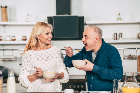 beautiful wife holding bowl with cornflakes near cheerful husband eating in kitchen