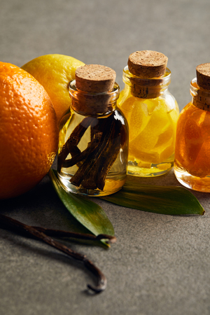Bottles of essential oil with lemon, orange and vanilla on dark surface