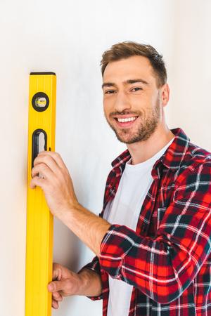 cheerful handyman holding measuring level at home Standard-Bild - 119070410